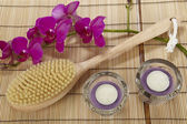 Bath brush, orchid and tealights on a mat of bamboo — Stock Photo