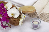Bath brush, rolled towels, tealight and orchids — Stock Photo