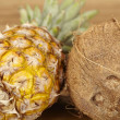Stock Photo: Pineapple and coconut on acacitabletop - close shot