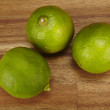 Stock Photo: Three limes on tabletop of acaciwood