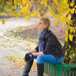 Stock Photo: Sad young woman sit near autumn tree