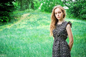 Sad woman stays in a forest's meadow — Stock Photo