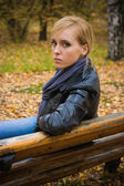 Young beautiful girl sit on a banch — Stock Photo