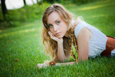 Beautiful girl lies on the grass — Stock fotografie