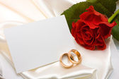 Wedding rings, rose and card — Stock fotografie