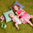 Stock Photo: Two sisters lie on carpet
