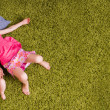 Stock Photo: Mother and two children lie on carpet