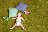 Little baby lies on green carpet — Stock Photo
