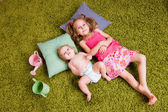Two sisters lie on carpet — Stock Photo