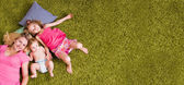Mother and two children lie on carpet — Stock Photo