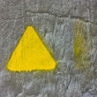 Stock Photo: Concrete gray wall with yellow triangle