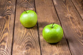 Two green apples on a wooden background — Stock Photo