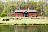 Red house by water — Stock Photo