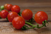 Cherry tomatoes on a wooden texture — Stock Photo