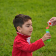 图库照片: Mother and son playing soap bubbles in park
