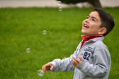 Child with soap bubbles in the park — Stock Photo