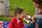 Child eating strawberries with his mother in the park — Stock Photo