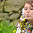Stock Photo: Young womblowing flower