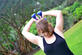 Woman with dumbbells in the park — Stockfoto