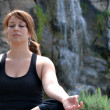 Stock Photo: Wompracticing yogwith waterfall background