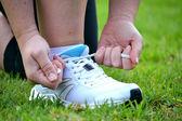 Broker woman tying running shoes — Stock Photo
