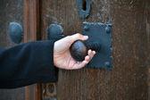 Woman opening an old wooden door — Stock Photo