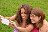 Friends taking picture wich camera phone — Stock Photo