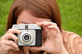 Young woman taking pictures with an old camera — Stock Photo