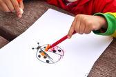 Child painting a ladybug — Stock fotografie