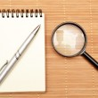 Notepad and magnifying glass — Stock Photo #46655553