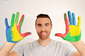 Man looking into the camera with painted hands — Stockfoto