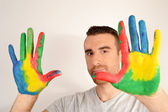 Man looking into the camera with painted hands — Stock Photo