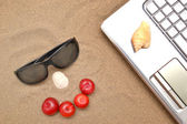 Laptop, plums and sunglasses — Stock Photo