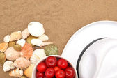 Red plums, shells and white hat on sand — Stock Photo