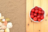 Plums and shells on wood and sand — Stock Photo