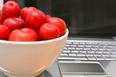 Laptop, plums and shells on wood and sand — Stock Photo