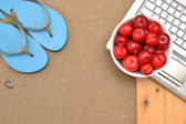 Slippers, laptop and plums on wood and sand — Stock Photo