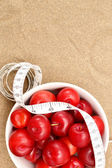 Red plums and tape measure — Stock Photo