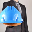 Businessman showing a helmet — Stock Photo #50299649