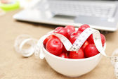 Red plums, laptop and tape measure on sand — Stock Photo