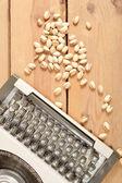 Typewriter and pistachios — Stock Photo