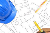 Helmet and tools for construction drawings — Stock Photo