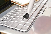 Brush cleaning a laptop — Stock Photo