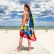 Tanned girl in bikini posing on the beach with colored pareos — Stock Photo #30152571