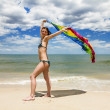 Tanned girl in bikini posing on the beach with colored pareos — Stock Photo #30152595