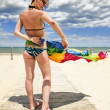 Tanned girl in bikini posing on the beach with colored pareos — Stock Photo
