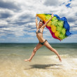 Tanned girl in bikini jumping on the beach with a colored scarf — Stock Photo