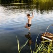 A boy jumps in a lake with a running start — Stock Photo