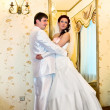 The groom embracing bride near the mirror — Stockfoto