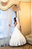 Bride in wedding dress looks out the window — Stock Photo